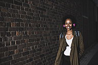 Smiling young woman in front of brick wall listening music with headphones - UUF09801