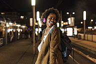 Smiling young woman with headphones and backpack waiting at the tram stop - UUF09807