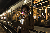 Portrait of smiling young woman with headphones and tablet waiting at the tram stop - UUF09813