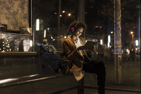 Young woman with headphones and tablet waiting at the tram stop - UUF09819