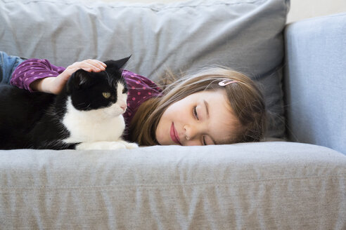 Little girl lying on couch stroking cat - LVF05788