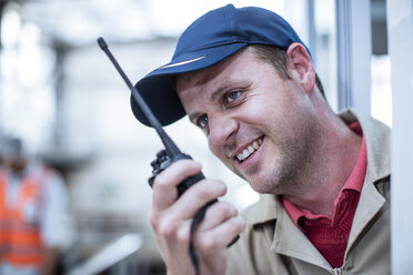 Smiling worker with walkie-talkie in factory - ZEF12435