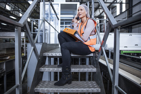 Female inspector on the phone sitting on stairs in factory - ZEF12438