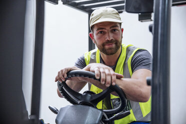 Portrait of confident man on forklift - ZEF12444