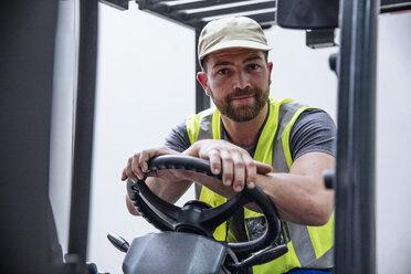 Portrait of confident man on forklift - ZEF12444