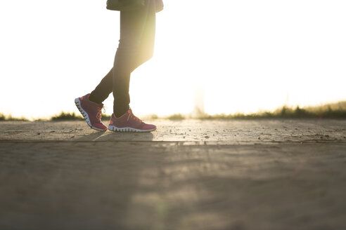 Woman wearing sneakers strolling at sunset, partial view - CHPF00365