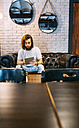 Stylish young man sitting on couch in a cafe using tablet - MGOF02811