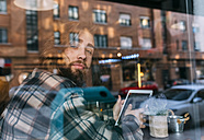 Portrait of stylish young man behind windowpane with tablet in a cafe - MGOF02814