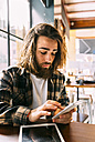 Stylish young man using cell phone in a cafe - MGOF02817
