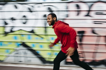 Smiling young man wearing red hoodie running along a graffiti wall - JRFF01162