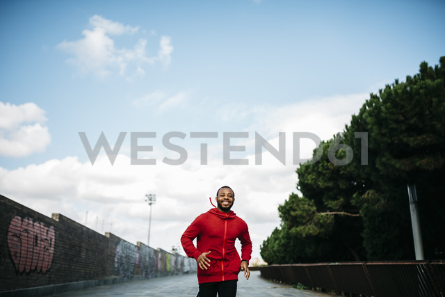 Smiling young man wearing red hoodie running in the city - JRFF01168