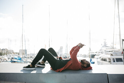Young man lying on a wall at the marina using cell phone - JRFF01171