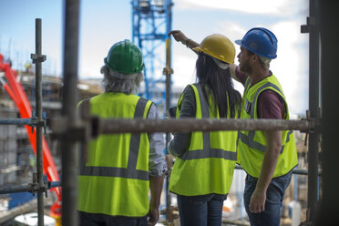 Construction worker talking to man and woman on a construction site - ZEF12466