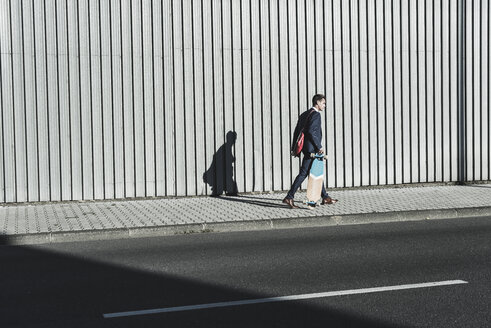 Young businessman walking with skateboard on pavement - UUF09821