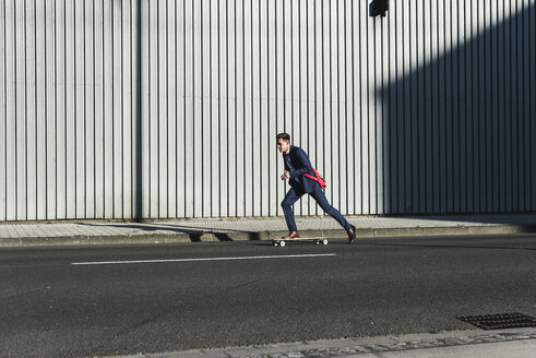 Young businessman riding skateboard on the street - UUF09824