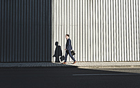 Young businessman walking on pavement - UUF09830