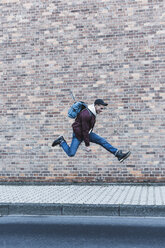 Young man jumping in front of brick wall - UUF09845