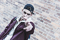 Portrait of young man gesturing in front of brick wall - UUF09851