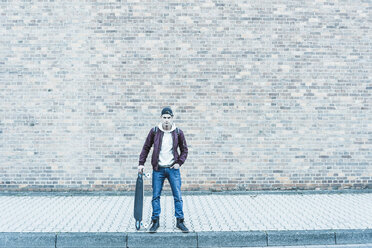 Portrait of young man with skateboard in front of brick wall - UUF09854