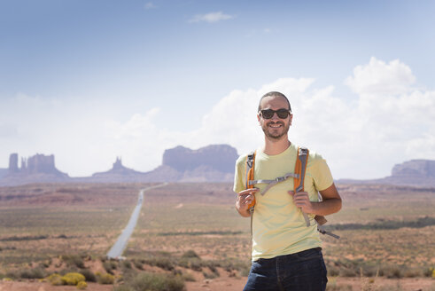 USA, Utah, portrait of smiling man with backpack and sunglasses on road to Monument Valley - EPF00277