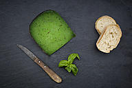 Piece of basil cheese, kitchen knife, slices of white bread and basil leaves on slate - LVF05794