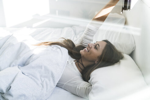 Smiling young woman lying in bed - KKAF00320