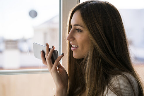 Young woman using cell phone at the window - KKAF00329