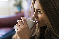 Young woman drinking coffee from cup - KKAF00341