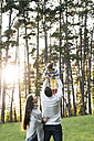 Playful parents with girl in forest - HAPF01301
