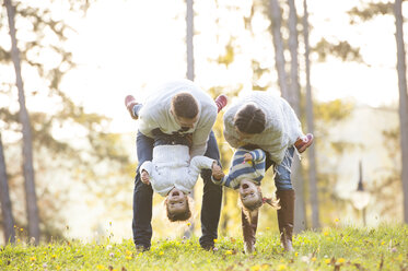 Playful family with two girls on meadow - HAPF01310