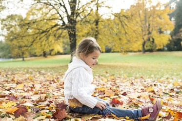 Girl sitting in autumn leaves - HAPF01319