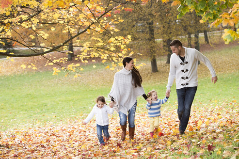 Happy family with two girls walking in autumn leaves - HAPF01322