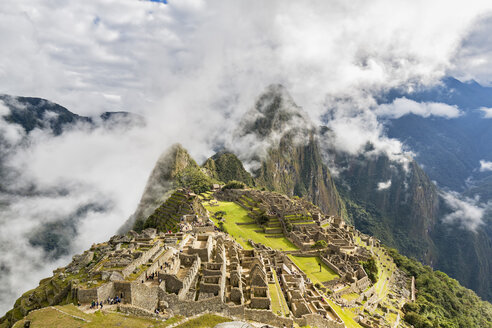 Peru, Andes, Urubamba Valley, Machu Picchu with mountain Huayna Picchu in fog and clouds - FOF08773