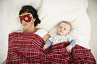 Mother with sleep mask and awake baby lying in bed - FSF00655