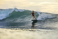 Indonesia, Bali, woman surfing on a wave - KNTF00614