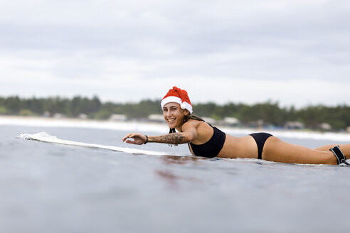 Indonesia, Bali, smiling woman on surfboard wearing Santa hat - KNTF00623