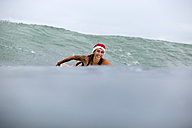 Indonesia, Bali, smiling woman on surfboard wearing Santa hat - KNTF00626