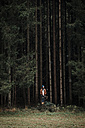 Young man standing in front of coniferous forest - WVF00811