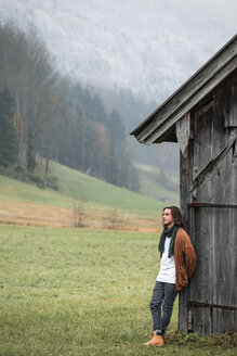 Austria, Mondsee, young man leaning against wooden hut on a meadow - WVF00814