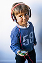 Little boy listening to music of his smartphone with headphones - VABF01050
