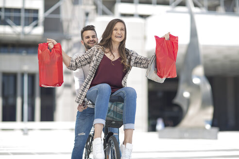 Happy young couple having fun in the city riding bicycle with shopping bags - ZEF12488