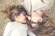 Mother and daughter lying on the carpet wearing funny glasses with plastic nose - RTBF00603