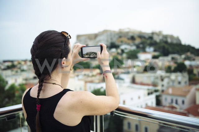 Greece, Athens, woman taking a cell phone picture of the Parthenon temple in the Acropolis surrounded by the city - GEMF01397 - Gemma Ferrando/Westend61