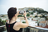 Greece, Athens, woman taking a cell phone picture of the Parthenon temple in the Acropolis surrounded by the city - GEMF01397