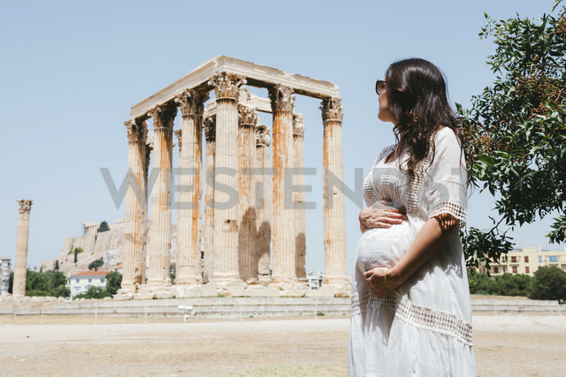 Greece, Athens, pregnant woman visiting the Olympieion with the Acropolis in the background - GEMF01415 - Gemma Ferrando/Westend61