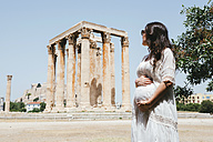 Greece, Athens, pregnant woman visiting the Olympieion with the Acropolis in the background - GEMF01415