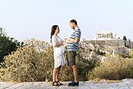 Greece, Athens, expectant parents showing the belly at Areopagus with The Acropolis and Parthenon in the background - GEMF01427