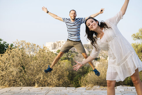 Greece, Athens, happy couple jumping at Areopagus with The Acropolis and Parthenon in the background - GEMF01430
