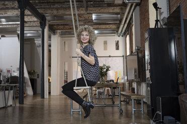 Smiling woman on swing in modern office - RBF05567