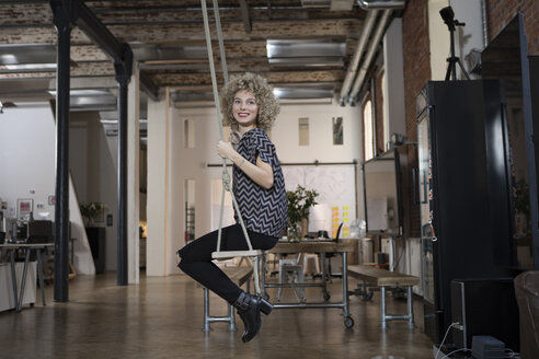 Smiling woman on swing in modern office - RBF05567